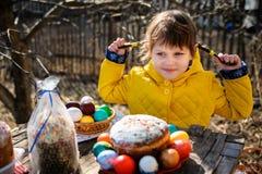 Une fille avec deux tresses se reposant dehors à une table en bois, looki Photographie stock