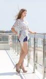 Une fille avec du charme et jeune sur un fond d'un hôtel de luxe près d'une mer Une belle dame dans le chemisier et des jeans cou photographie stock libre de droits