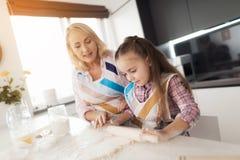 Une fille avec une grand-mère déroulant une pâte pour un tarte fait maison Image libre de droits