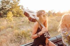 Une fille avec une guitare dans la voiture Images stock