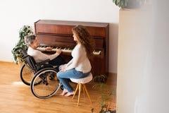 Une fille avec la grand-mère dans le fauteuil roulant jouant le piano Image stock
