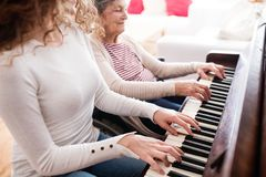 Une fille avec la grand-mère dans le fauteuil roulant jouant le piano Photos stock