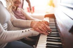 Une fille avec la grand-mère jouant le piano Image stock
