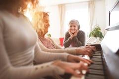 Une fille avec la mère et la grand-mère jouant le piano Photos stock