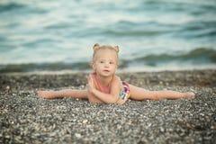 Une fille avec la trisomie 21 se reposant sur les fentes Photographie stock libre de droits