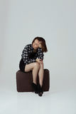 Une fille avec la valise attendant quelqu'un photographie stock libre de droits