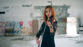 Une fille avec le violon en bois exécute dans une salle vide banque de vidéos