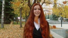 Une fille avec les cheveux rouges débordants se tient sous les feuilles en baisse en parc banque de vidéos