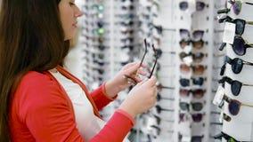 Une fille avec une queue sur ses cheveux se tient parmi les rangées avec des lunettes de soleil Essayez les verres élégants et re banque de vidéos