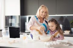 Une fille avec sa grand-mère fait cuire un gâteau fait maison Ils mettent dessus des tabliers de cuisine et malaxent la pâte Photographie stock