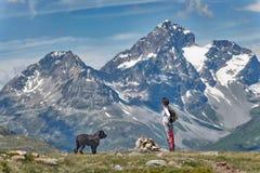 Une fille avec son grand chien noir dans la montagne rentre la vue Images libres de droits