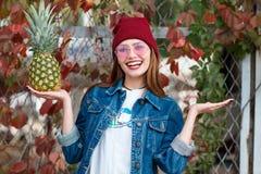 Une fille avec un ananas se tient sur la rue sur un fond d'automne Images stock
