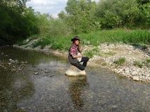 Une fille avec un banjo se reposant sur une roche images libres de droits