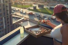 Une fille avec un beau sein dans un costume de sports va manger de la pizza et boire le mojito sur le fond de ville de coucher du photo stock