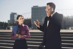 Une fille avec un dossier et un microphone attend l'homme pour cesser de parler au téléphone Photographie stock