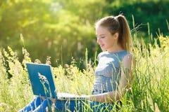 Une fille avec un ordinateur portable en nature parmi l'herbe verte image stock