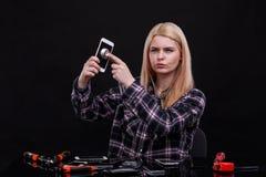 Une fille, avec un regard sérieux, écoute un smartphone avec un écran cassé par un stéthoscope Photos libres de droits