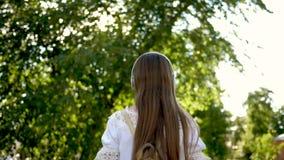 Une fille avec un sac à dos marche en parc avec des écouteurs et écoute la musique et les sourires ondulant sa main et ondulant a clips vidéos