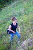 Une fille avec un sac à dos monte la colline Repos actif sur la nature images stock