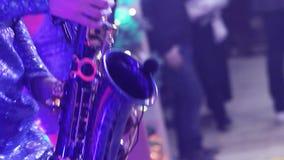 Une fille avec un saxophone, un groupe musical de filles avec un saxophone exécutent sur l'étape, une robe bleue, une lumière d'é banque de vidéos