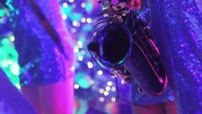 Une fille avec un saxophone, un groupe musical de filles avec un saxophone exécutent sur l'étape, une robe bleue, une lumière d'é clips vidéos