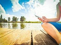 Une fille avec un téléphone dans sa main s'assied sur la surface en bois images stock