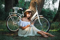 Une fille avec un téléphone s'assied sous un arbre Photos libres de droits