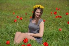 Une fille avec une guirlande des pissenlits sur sa tête Belle jeune fille féerique dans un domaine parmi les fleurs des tulipes Image stock