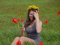 Une fille avec une guirlande des pissenlits sur sa tête Belle jeune fille féerique dans un domaine parmi les fleurs des tulipes Photographie stock