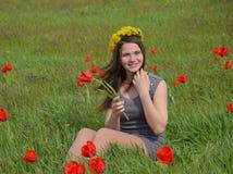 Une fille avec une guirlande des pissenlits sur sa tête Belle jeune fille féerique dans un domaine parmi les fleurs des tulipes Images libres de droits