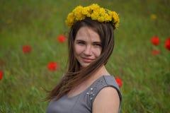 Une fille avec une guirlande des pissenlits sur sa tête Belle jeune fille féerique dans un domaine parmi les fleurs des tulipes Photographie stock libre de droits