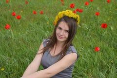 Une fille avec une guirlande des pissenlits sur sa tête Belle jeune fille féerique dans un domaine parmi les fleurs des tulipes Photos stock