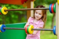 Une fille ayant l'amusement à un terrain de jeu Photographie stock