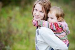 Une fille ayant une conduite de ferroutage sur sa maman Photographie stock libre de droits