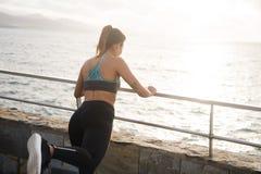 Une fille bien faite se tenant sur une balustrade par la mer Images stock