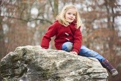 Une fille blonde d'enfant mignon posant sur une roche dehors Photo stock