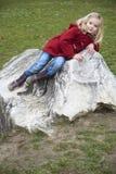 Une fille blonde d'enfant mignon posant sur une roche dehors Photographie stock libre de droits