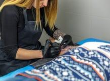 Une fille blonde de tatoueur dessine avec sa machine de tatouage, l'outl Images libres de droits