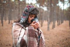 Une fille boit une boisson chaude d'une tasse dans une forêt d'automne photo stock
