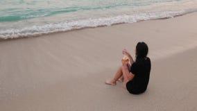 Une fille boit un cocktail sur une plage sablonneuse banque de vidéos