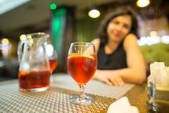 Une fille boit une boisson rouge de fraise dans un restaurant Photos libres de droits