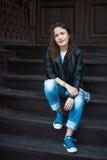 Une fille calme dans les espadrilles, les jeans et une veste en cuir s'assied sur le bois Photographie stock