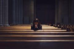 Une fille chrétienne est se reposante et priante avec le coeur brisé dans Image libre de droits
