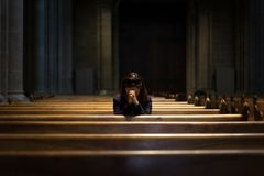 Une fille chrétienne est se reposante et priante avec le coeur brisé dans Photo stock
