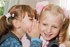 Une fille chuchote dans l'oreille de sa amie Photographie stock