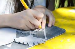 Une fille a coupé un couteau de carton avec le couteau de papeterie photographie stock