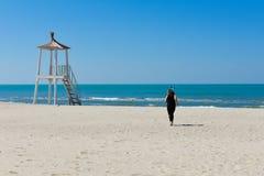 Une fille court sur la plage et apprécie le sentiment photo libre de droits