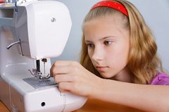 Une fille d'adolescent apprend à fileter une aiguille dans une machine à coudre moderne Image libre de droits