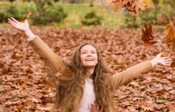 Une fille d'adolescent dans un manteau rit et jette des feuilles en automne photos libres de droits