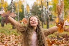 Une fille d'adolescent dans un manteau rit et jette des feuilles en automne images stock